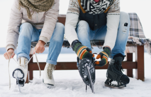 two people lacing their ice skates